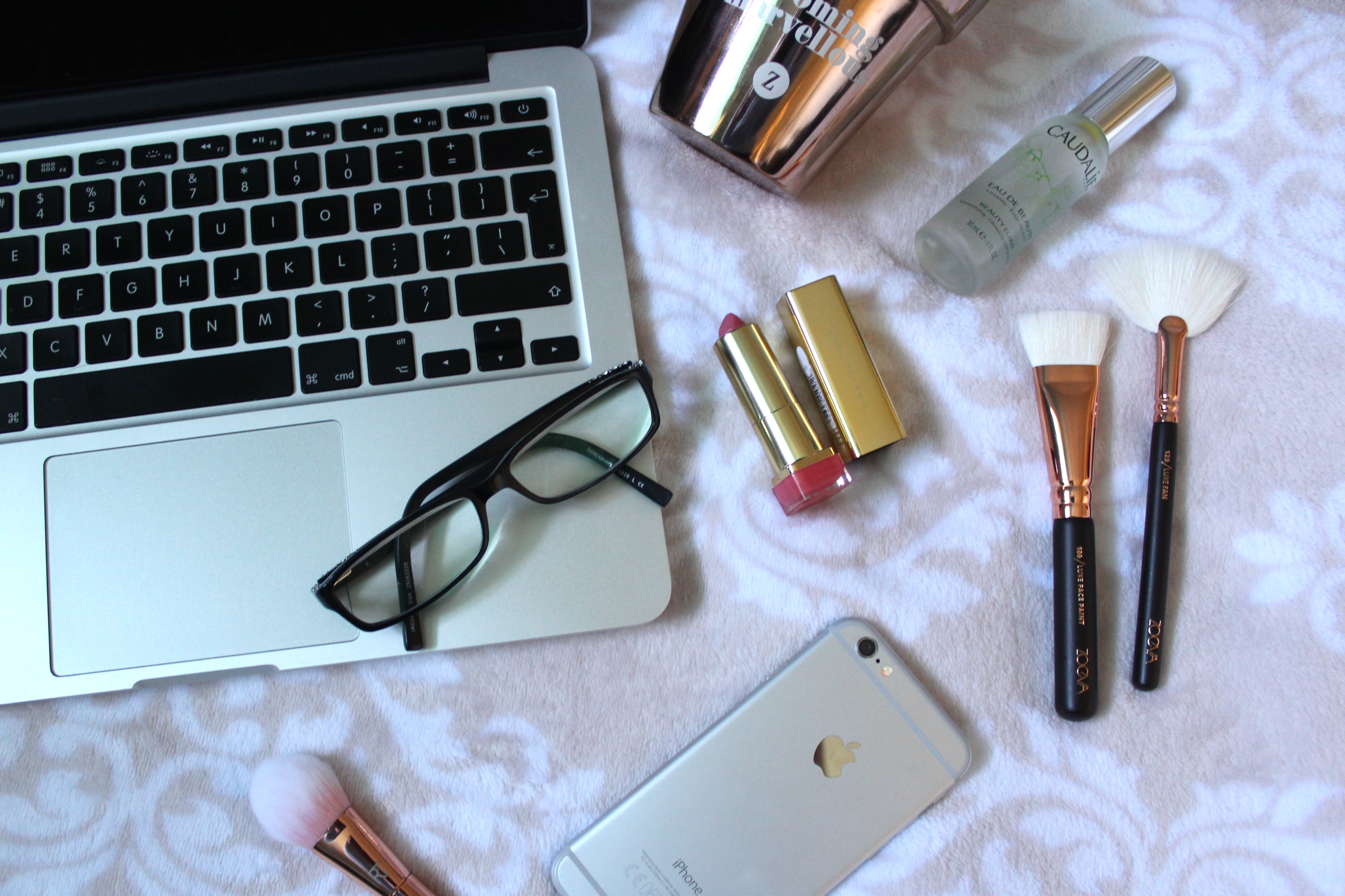 How to tell people about your blog - an image of a macbook, iphone, a few makeup brushes and a lipstick
