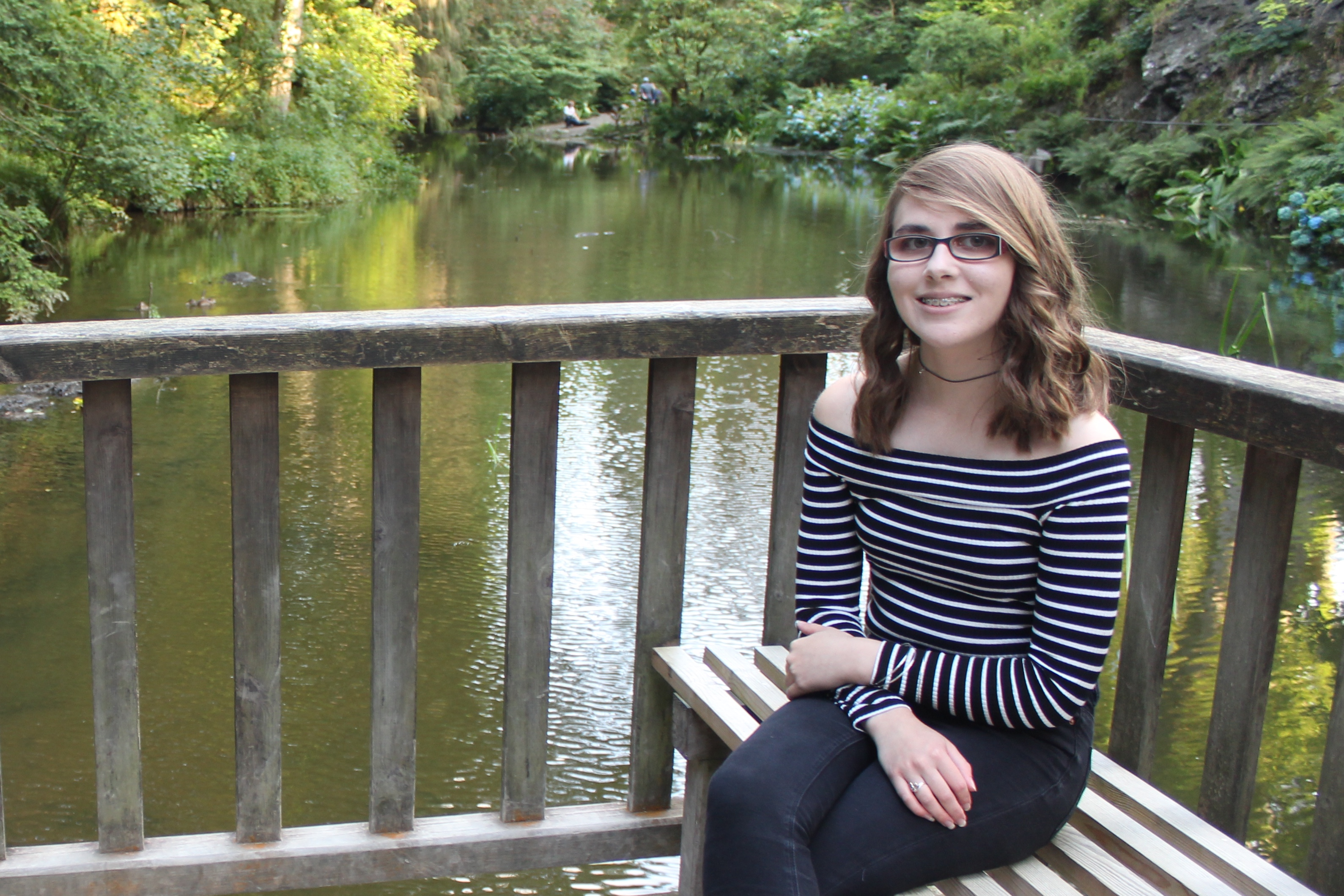 The reality of losing sight: A photo of Elin sitting on a bench in front of the river