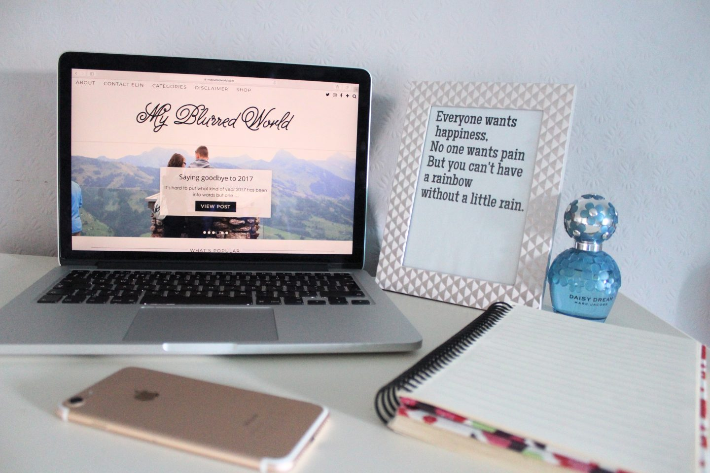 A photo of my blog on a macbook, there is a quote in a frame next to it that says everyone wants happiness, no one wants pain but you can't have a rainbow without a little rain