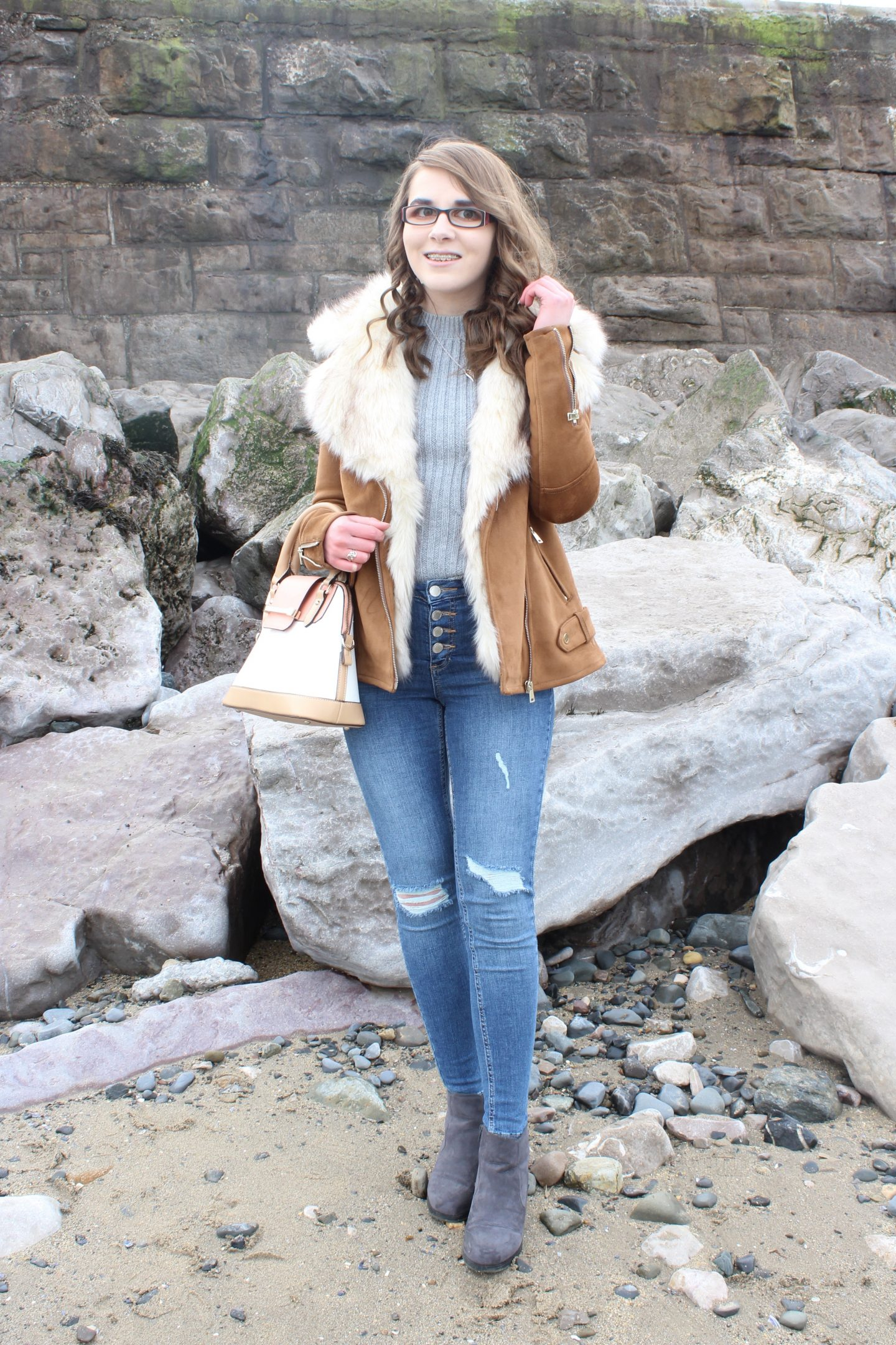 A photo of Elin wearing a tan faux suede and faux fur trim jacket, a grey knitted jumper, blue ripped jeans, grey ankle boots and a cream, peach and tan handbag