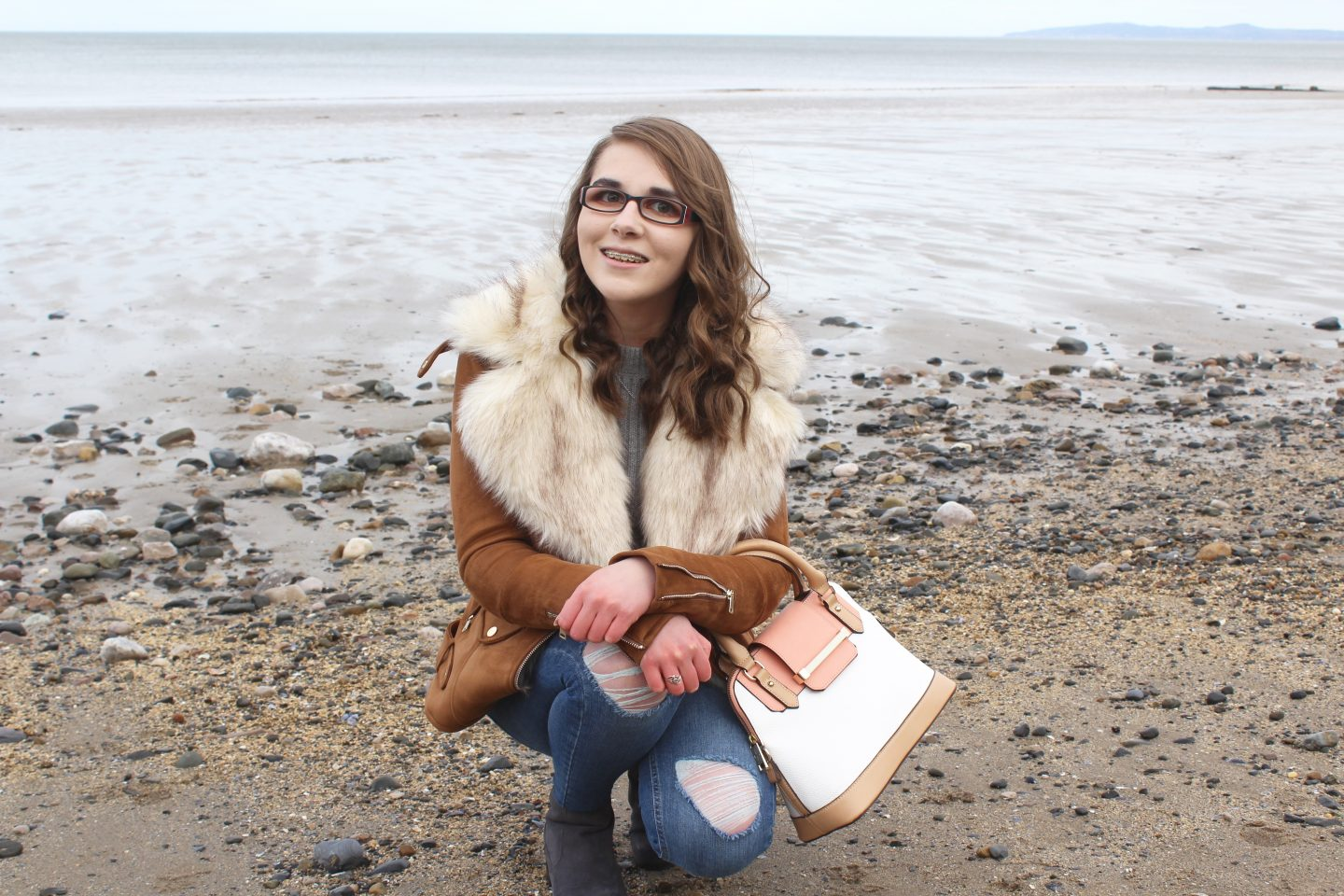 A photo of Elin on the beach, she is kneeling down and smiling at the camera