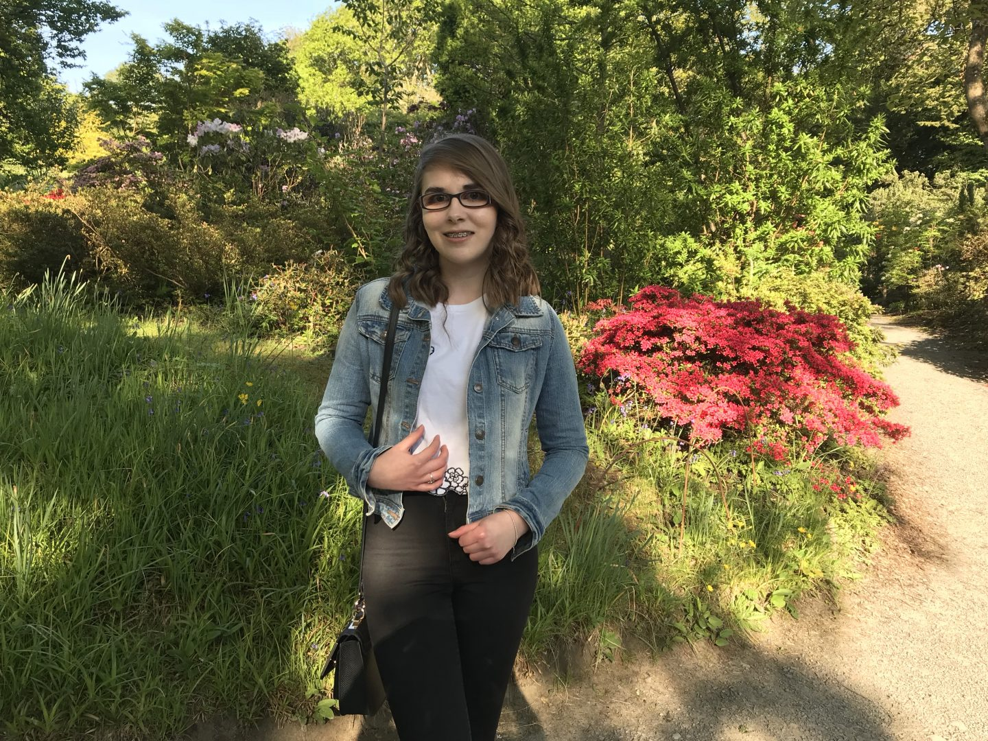 A photo of Elin in front of trees and flowers