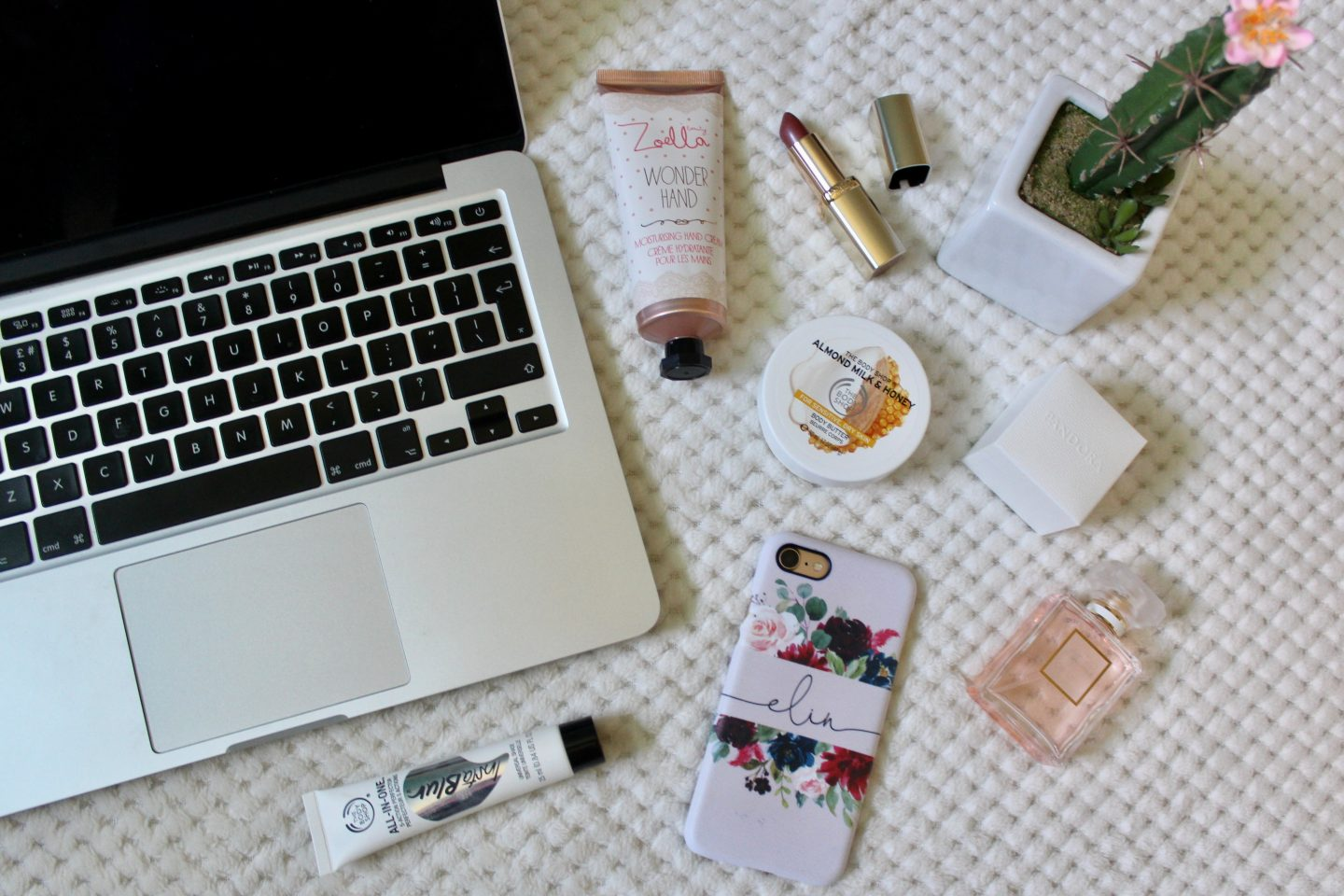 A photo of a macbook keyboard with beauty products around it and my phone which has a pink case and my name on it