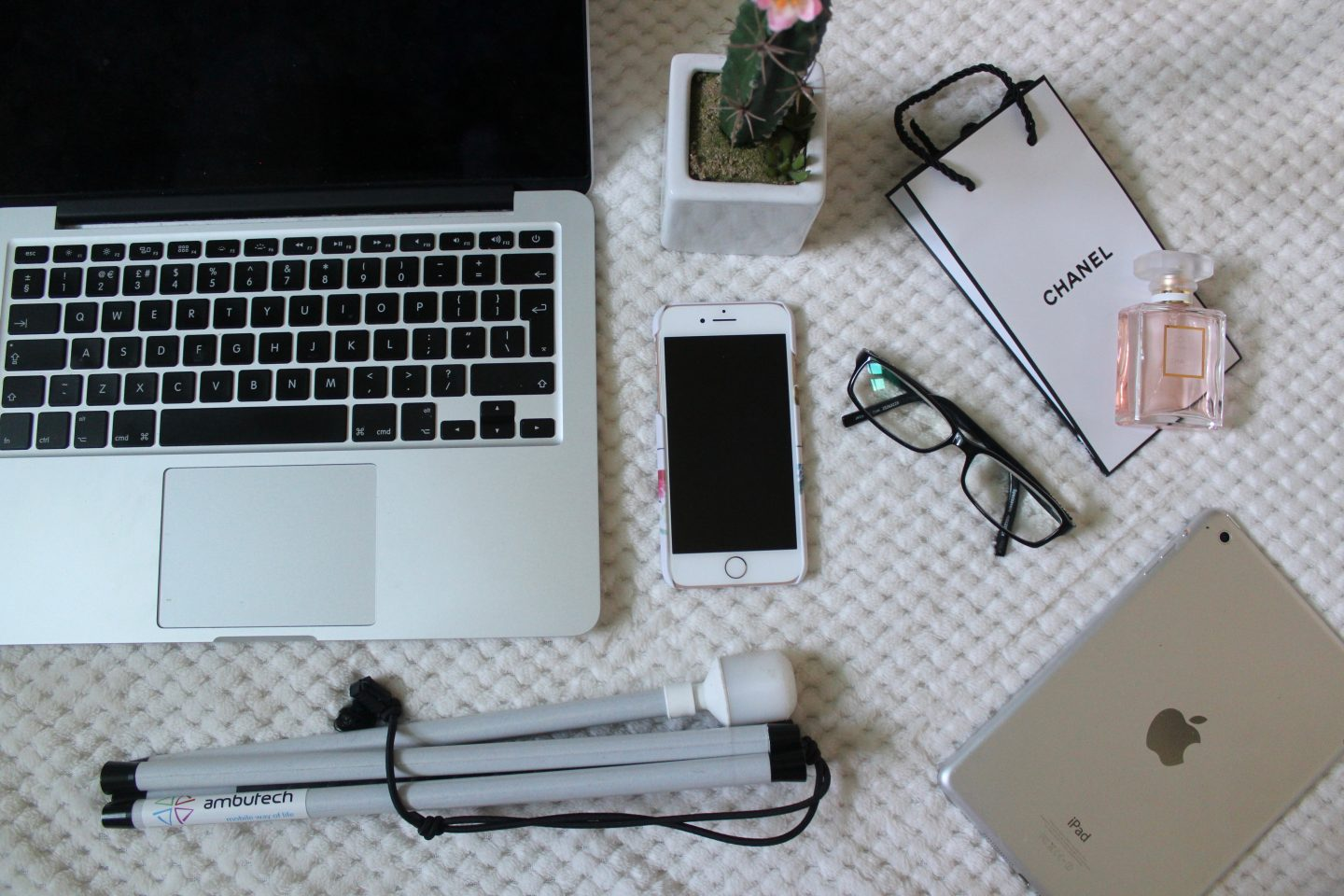 A photo of a macbook, white cane, iphone and ipad