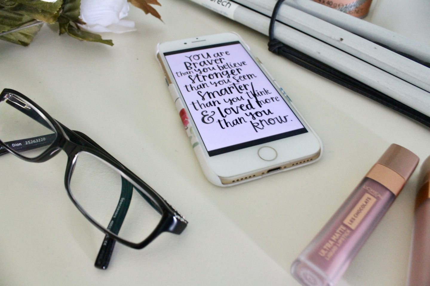 A photo of a black pair of glasses with my phone beside it which has a quote which says 'you're braver than you believe, stronger than you seem, smarter than you think and loved more than you know'.