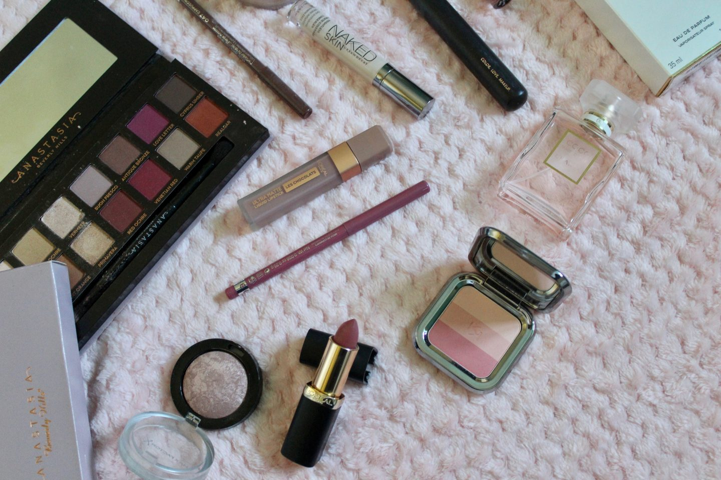 A photo of the anastasia beverly hills modern renaissance palette, a couple of l'oreal lipsticks, the chanel coco mademoiselle perfume and a few other beauty products