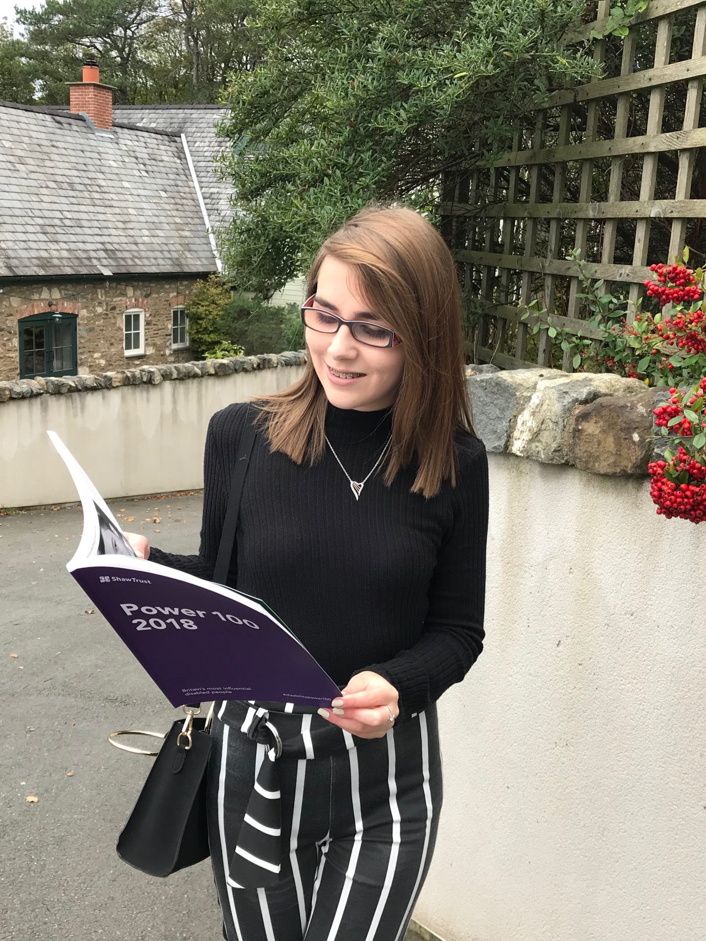 A photo of Elin holding the power list as if she's reading it