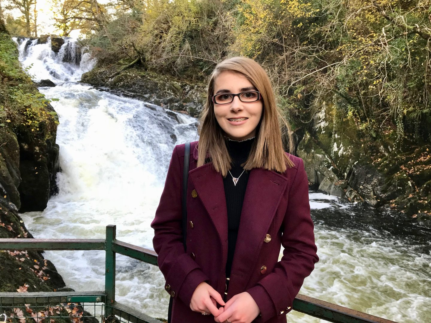 A photo of Elin in front of a waterfall