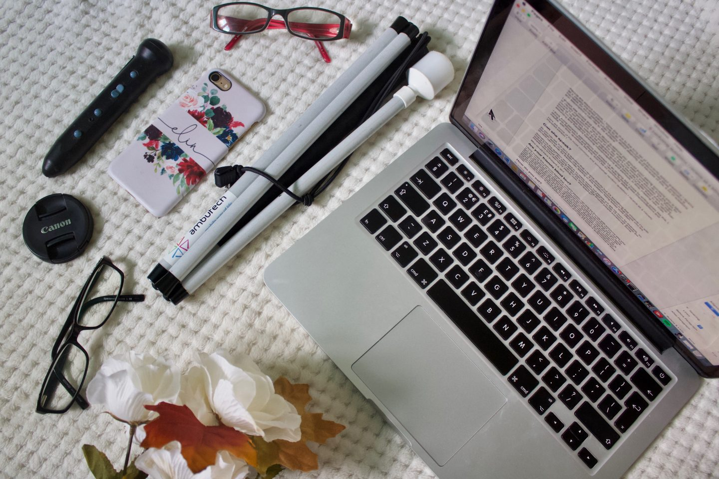 A photo of a macbook with a document open on it, my white cane, the penfriend labeller and two pairs of glasses. There is also a bunch of artificial flowers in the bottom corner of the photo.