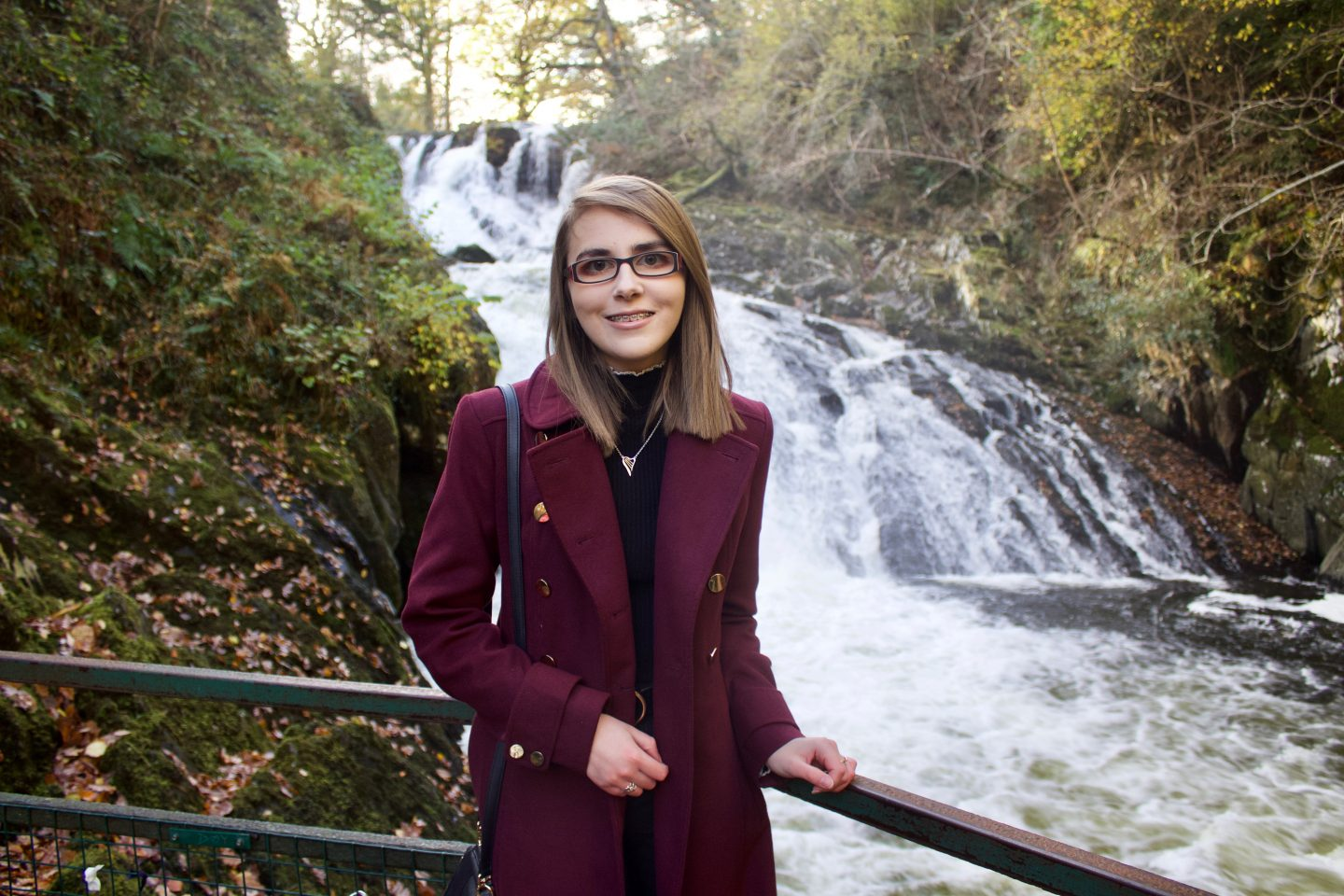 Learning to accept my differences: A photo of Elin wearing a burgundy long line coat standing in front of a waterfall