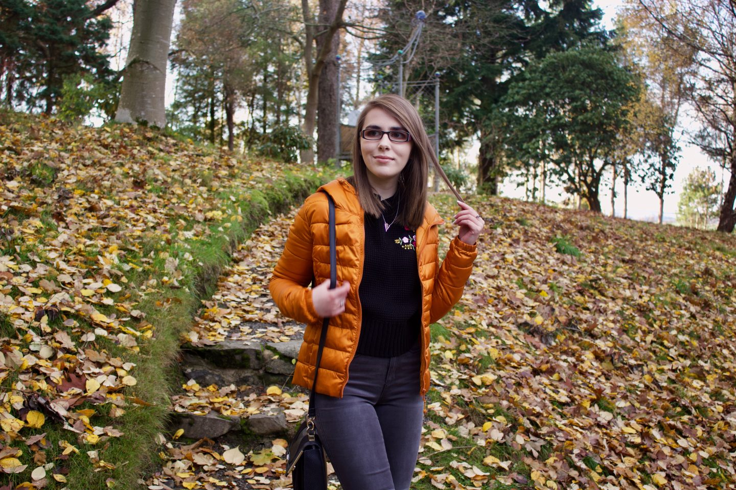 A photo of Elin wearing a black knitted jumper and orange/marmelade coloured quilted jacket, she is standing on some steps in a woodland and there are colourful leaves on the floor around her, her hand is up, holding a strand of hair and she is looking away from the camera
