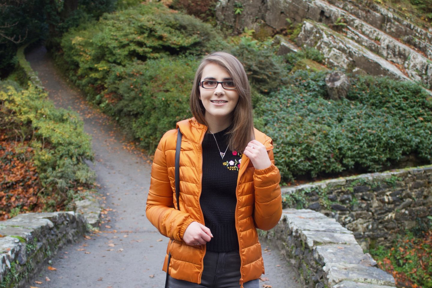 A photo of Elin wearing a black knitted jumper, an orange quilted jacket and a harp shaped necklace