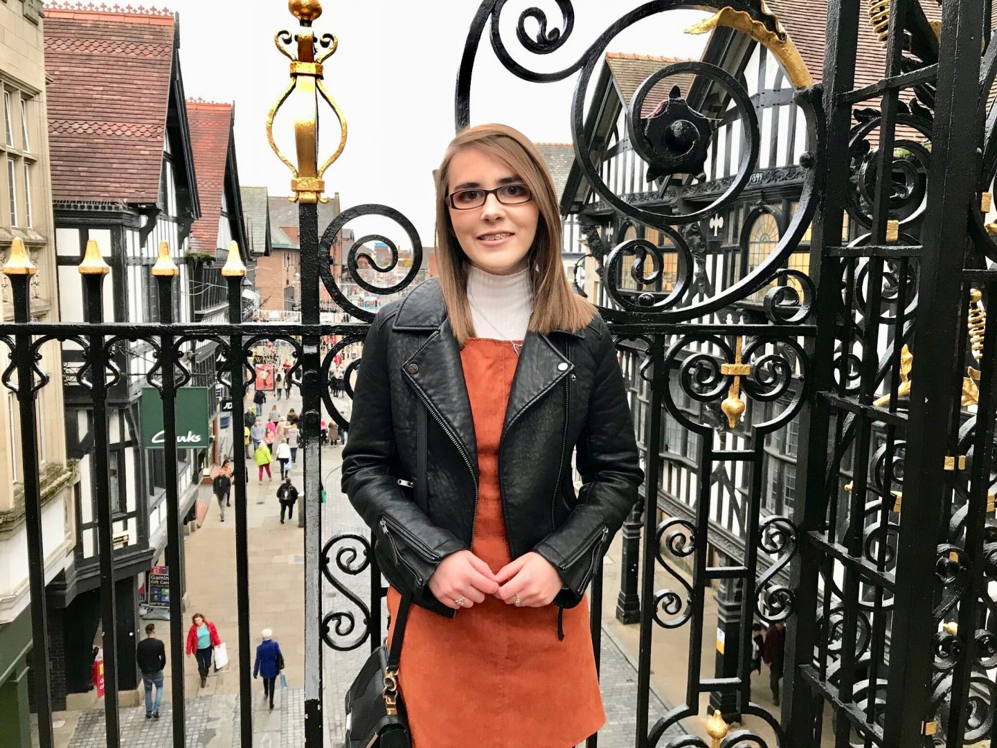 Life as a 20 year old VI girl: A photo of Elin in a burnt orange pinafore and black leather jacket. She is standing in front of pretty black railings with a street in the background