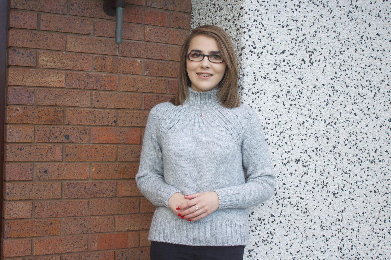 A photo of Elin wearing a light grey high neck jumper
