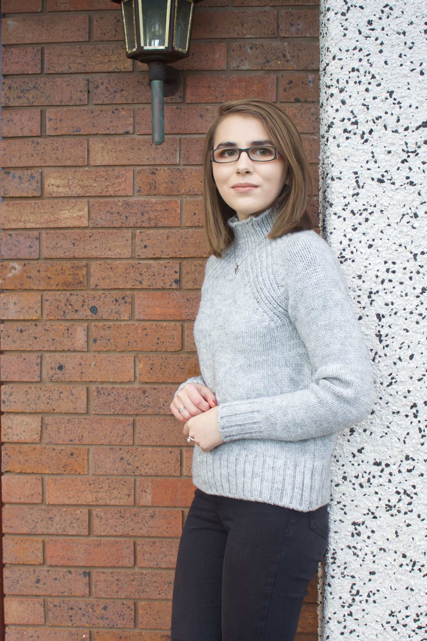 A photo of Elin from the side, she is leaning against a wall