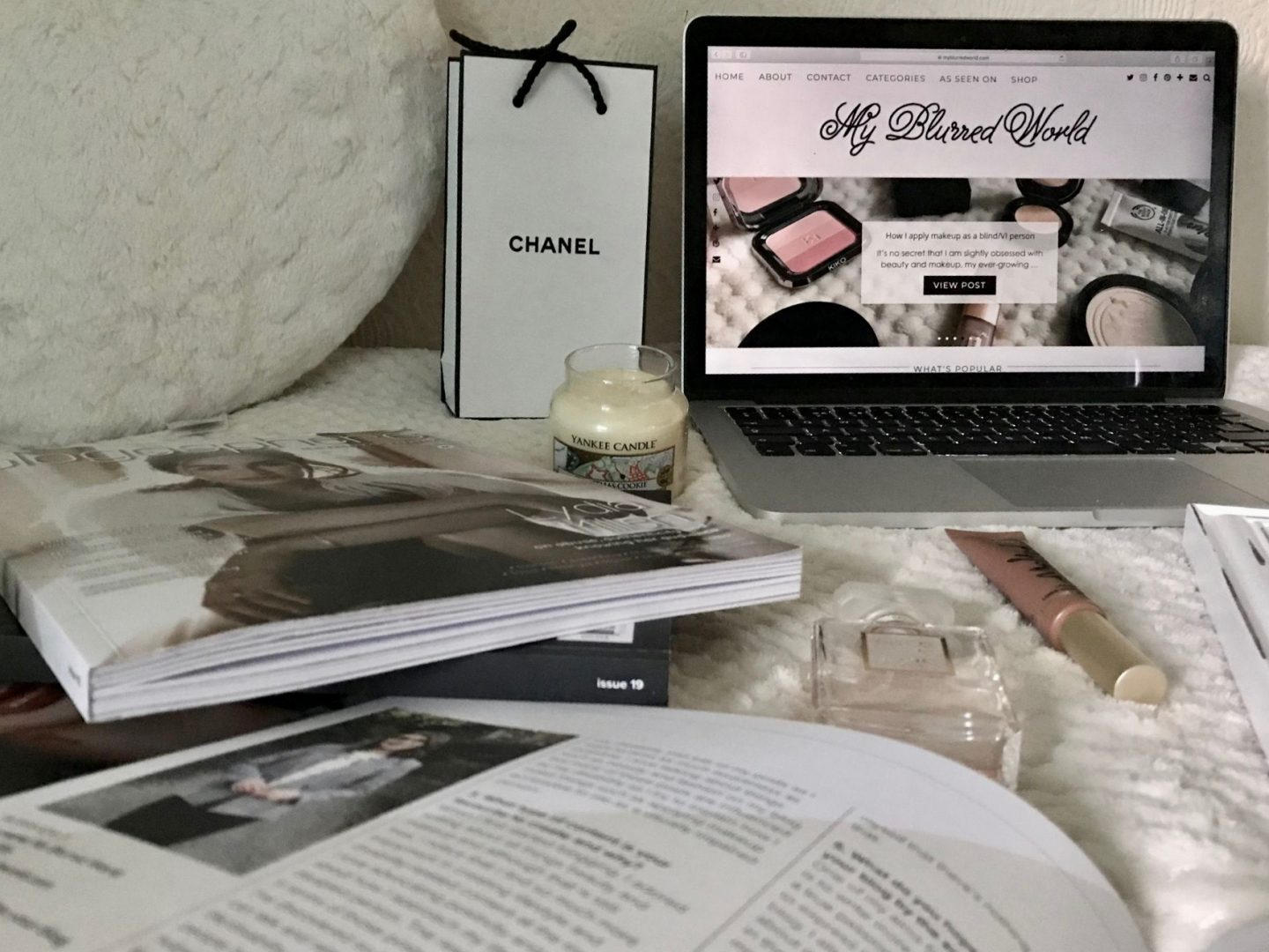 A photo of my blog on a laptop, my page in the June edition of Blogosphere magazine, other issues of blogosphere, a couple of beauty products and a chanel perfume bag beside my laptop