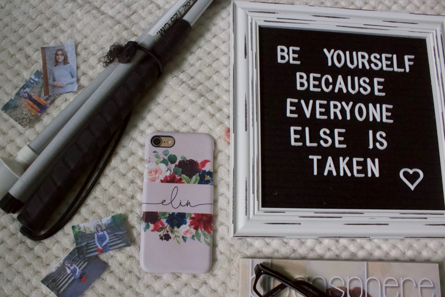A photo of a felt letter board with a personalised phone case beside it and my white cane