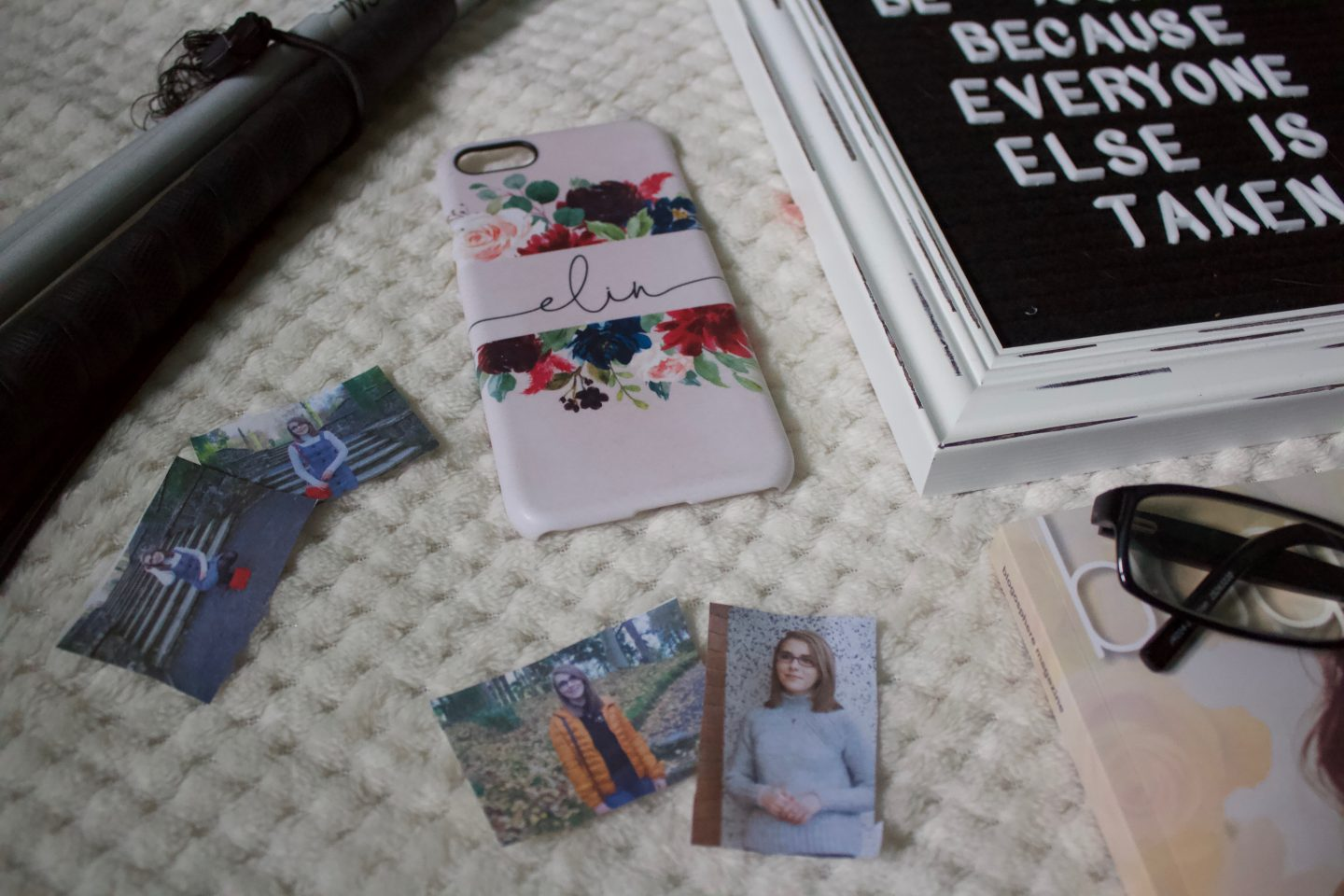 A photo which shows a personalised pink phone case and some small print out photos of me