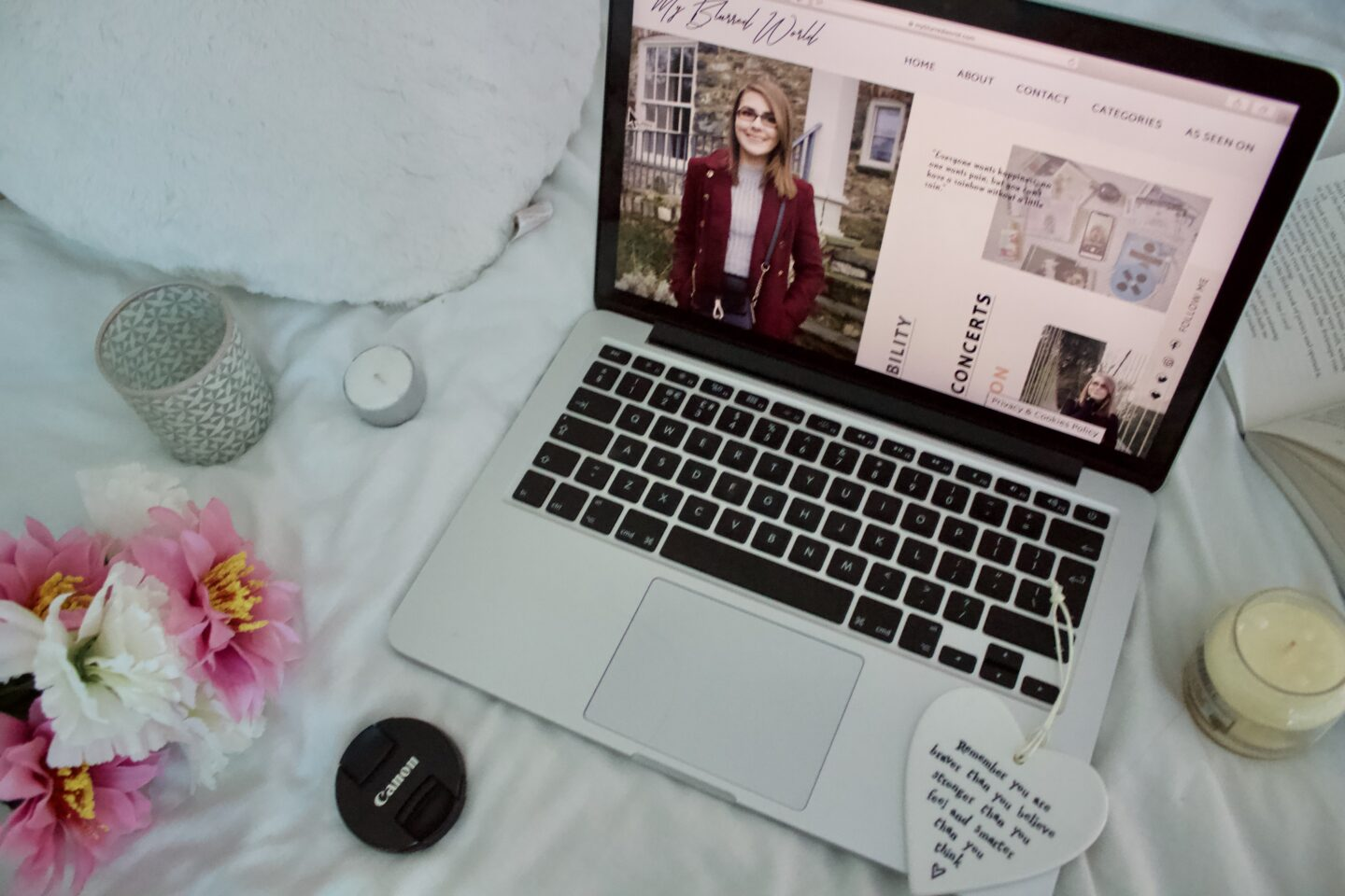 My Blurred World's homepage showing on an open laptop screen, the laptop is surrounded by miscellaneous items such as a couple of candles, a heart shaped hanging ornament, fake flowers and an open book