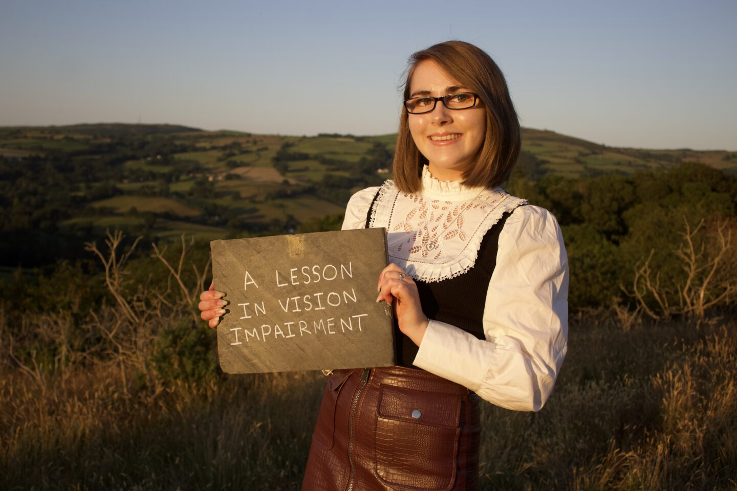 Elin holding a slate which has the blog post title written in white on it. The setting sun casts her profile in a golden glow. She wears a white victorian style top which has long puff sleeves and a faux leather mini skirt. She's smiling at the camera.